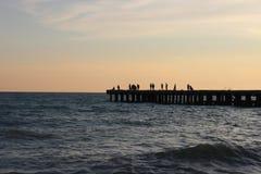 Силуэты людей, вероятно рыболовов на пристани в море стоковые изображения rf