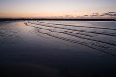 Силуэты людей на выравнивать пляж стоковые фотографии rf
