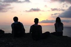 Силуэты людей на заходе солнца Стоковое Изображение RF