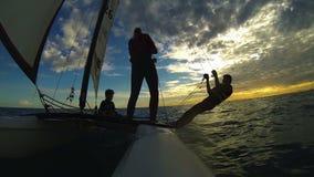 Силуэты 3 людей плавая на катамаране виндсерфинга против неба захода солнца сток-видео