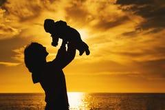 Силуэты матери и младенца на заходе солнца на море приставают к берегу Стоковая Фотография
