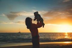 Силуэты матери и младенца на заходе солнца на море приставают к берегу Стоковые Фото