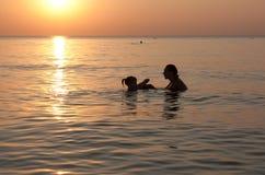 Силуэты матери с младенцем играя в море стоковое фото rf