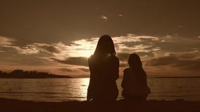 Силуэты мать и дочь сидят на пляже на заходе солнца Концепция дружелюбной семьи, образ жизни видеоматериал