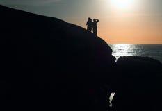 Силуэты на заходе солнца стоковые изображения rf