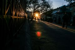 Силуэты на темной улице на back-light Солнця на заходе солнца Стоковая Фотография RF