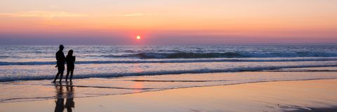 Силуэты пары наслаждаясь заходом солнца на Атлантическом океане, Lacanau Франции Стоковое Изображение