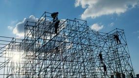 Силуэты работника инженера людей на строительной площадке Работники на построителях захода солнца собирают дизайн Здание концепци акции видеоматериалы