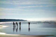 Силуэты семьи на пляже стоковые изображения rf