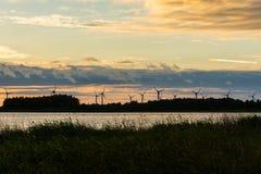 Силуэты станций энергии ветра в ряд на восточном побережье  Стоковая Фотография RF
