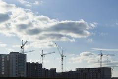 Силуэты строительной площадки с незаконченными зданиями и кранами против неба с облаками стоковая фотография rf