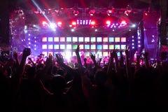 Силуэты толпы, группы людей, веселя в концерте живой музыки перед красочными светами этапа стоковые изображения
