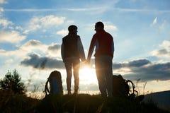 Силуэты человека и женщины смотря один другого, держа руки против захода солнца в горах Стоковая Фотография RF