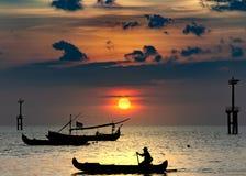 Силуэты шлюпок в порте на заходе солнца Рыболов на шлюпке пошел к рыбной ловле ночи, силуэту rower в шлюпке стоковые изображения rf