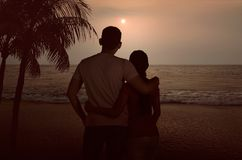 Силуэт азиатских пар обнимая и наслаждаясь заход солнца совместно Стоковое Фото