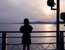 Силуэт азиатской женщины стоя около поляка на крае парка около океана  стоковое фото rf