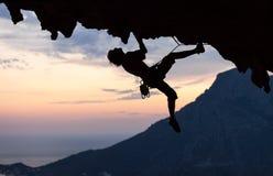 Силуэт альпиниста утеса на заходе солнца Стоковое Изображение