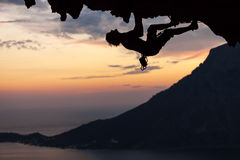 Силуэт альпиниста утеса на заходе солнца Стоковые Фото