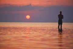 Силуэт атлетического человека против моря и захода солнца Стоковая Фотография