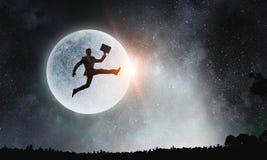 Силуэт бизнесмена над луной Мультимедиа стоковые изображения rf
