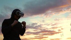 Силуэт боксера молодого человека в тренировке шлемофона VR 360 для пинать в бое виртуальной реальности на заходе солнца на парке  Стоковое Изображение