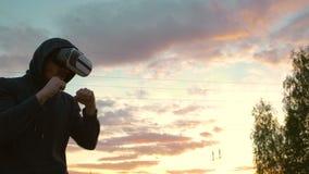 Силуэт боксера молодого человека в тренировке шлемофона VR 360 для пинать в бое виртуальной реальности на заходе солнца на парке  Стоковые Фото