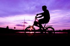 Силуэт велосипеда езды велосипедиста на дороге на заходе солнца Стоковое фото RF