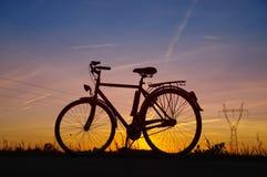 Силуэт велосипеда на заходе солнца Стоковое Изображение