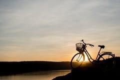 Силуэт велосипеда на предпосылке захода солнца Стоковые Изображения RF