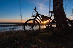 Силуэт велосипеда стоя около дерева против фона заходящего солнца Стоковая Фотография RF