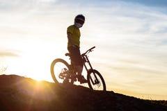Силуэт велосипедиста в шлеме стоя с горным велосипедом на утесе на заходе солнца Весьма концепция спорта Стоковая Фотография