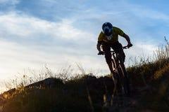 Силуэт велосипедиста ехать вниз с горного велосипеда на скалистом холме на заходе солнца Весьма концепция спорта Стоковые Изображения RF