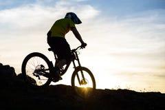 Силуэт велосипедиста ехать вниз с горного велосипеда на скалистом холме на заходе солнца Весьма концепция спорта Стоковое фото RF