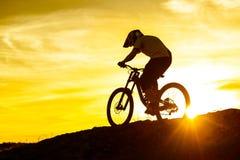 Силуэт велосипедиста ехать вниз с горного велосипеда на скалистом холме на заходе солнца Весьма концепция спорта Стоковые Фото