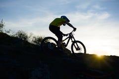 Силуэт велосипедиста ехать вниз с горного велосипеда на скалистом холме на заходе солнца Весьма концепция спорта Стоковые Фотографии RF