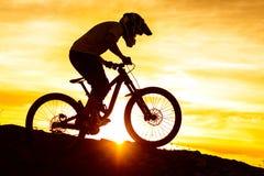 Силуэт велосипедиста ехать вниз с горного велосипеда на скалистом холме на заходе солнца Весьма концепция спорта Стоковые Изображения