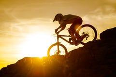Силуэт велосипедиста ехать вниз с горного велосипеда на скалистом холме на заходе солнца Весьма концепция спорта Стоковое Изображение RF