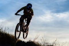 Силуэт велосипедиста ехать вниз с горного велосипеда на скалистом холме на заходе солнца Весьма концепция спорта Стоковое Фото