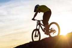 Силуэт велосипедиста ехать вниз с горного велосипеда на скалистом холме на заходе солнца Весьма концепция спорта Стоковое Изображение