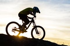 Силуэт велосипедиста ехать вниз с горного велосипеда на скалистом холме на заходе солнца Весьма концепция спорта Стоковая Фотография RF