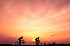 Силуэт велосипедистов едет велосипед на предпосылке захода солнца стоковое фото rf