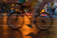 Силуэт велосипедистов катания на проезжей части города, свете ночи, bokeh, конце-вверх колес и ногах, конспекте, движении Стоковые Фотографии RF