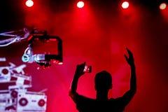 Силуэт вентилятора с поднятыми руками вверх, во время концерта стоковое изображение rf