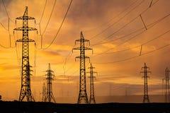 Силуэт высоковольтных столбов на заходе солнца Норильск стоковое фото