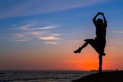 Силуэт гибкой девушки на морском побережье во время захода солнца танцулька Стоковая Фотография RF