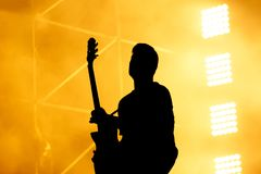 Силуэт гитариста, гитариста выполняет на этапе концерта Стоковые Изображения RF
