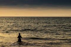 Силуэт девушки в воде на пляже Cabo Ledo Ангола, Африка стоковые фото