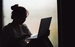 Силуэт девушки используя компьтер-книжку компьютера Стоковое Изображение RF