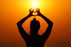 Силуэт девушки на заходе солнца Стоковые Изображения RF