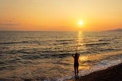 Силуэт девушки на предпосылке моря захода солнца Стоковые Фотографии RF